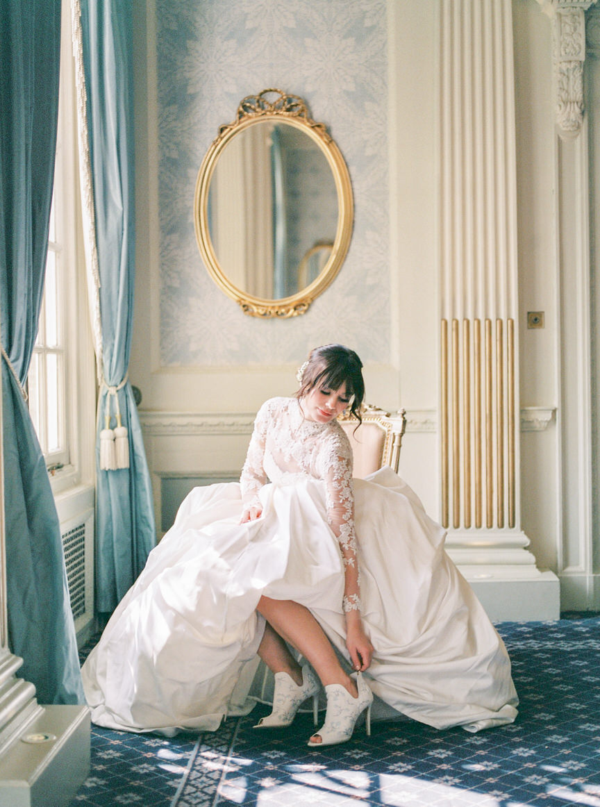 Bride in wedding dress putting wedding shoes on in room with golden mirror